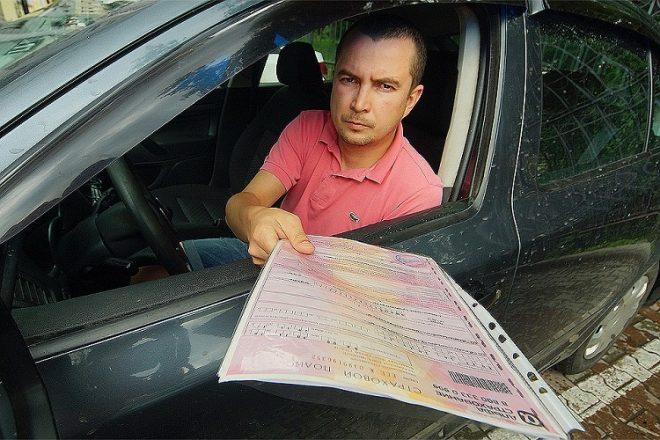 Водитель показывает полис ОСАГО