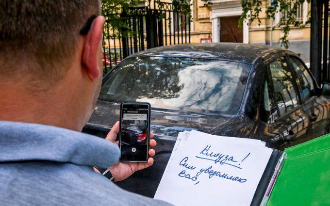 Мужчина фотографирует машину нарушителя