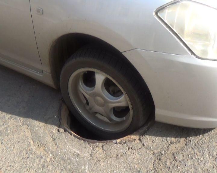 Колесо машины в люке