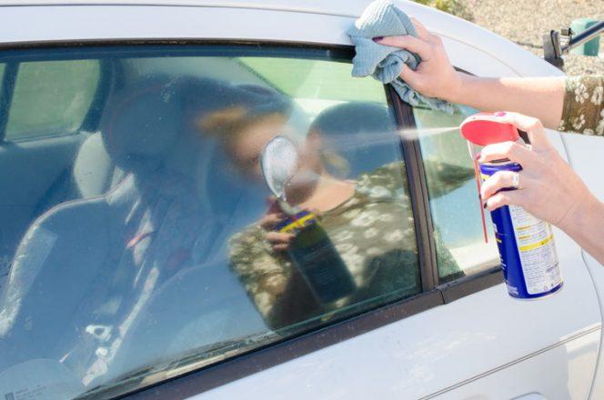 Мужчина распыляет ВД-40 на стекло