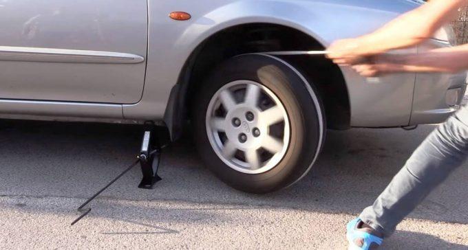 Человек тянет веревкой колесо