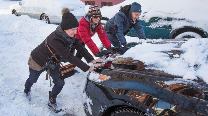 Люди толкают машину зимой
