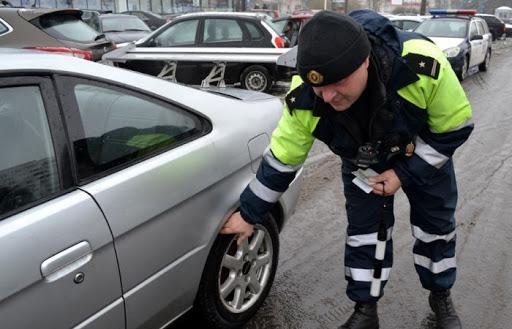 Инспектор проверяет колеса авто