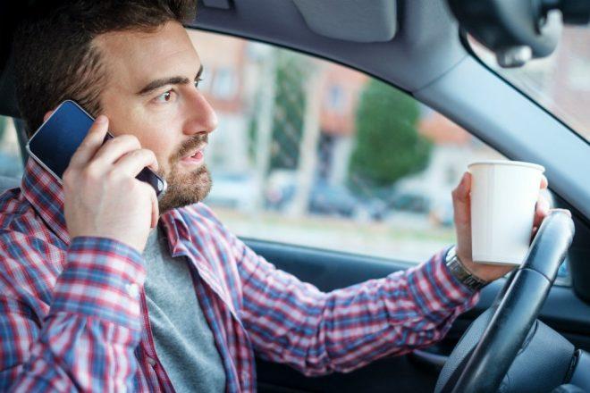 Мужчина за рулем разговаривает по телефону