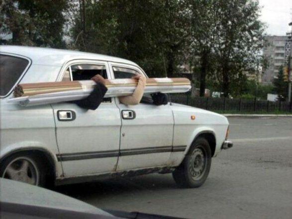 Люди держат доски из окон авто