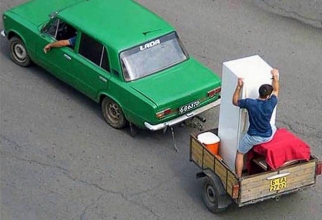 Мужчина держит холодильник в прицепе авто