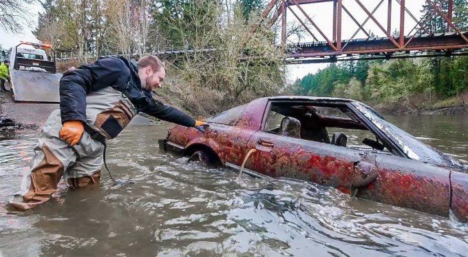 Мужчина вылавливает автомобиль в реке