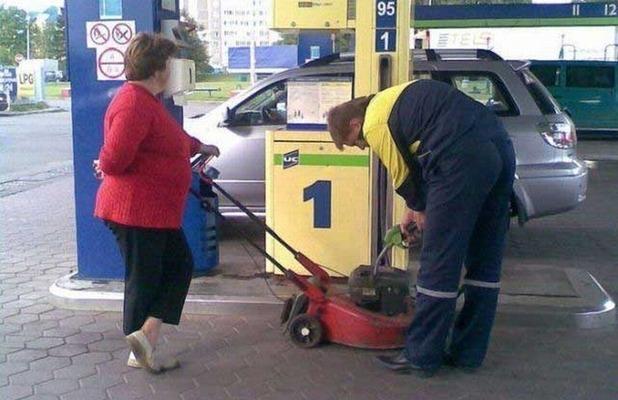 Мужчина заливает бензин в газонокосилку