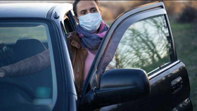 Женцина в маске садится в машину