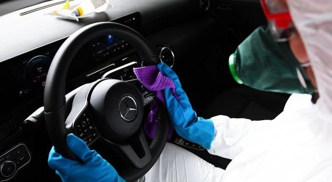 Мужчина в маске и костюме вытирает руль авто
