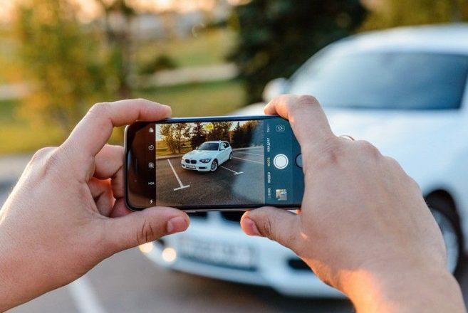 Мужчина фотографирует машину
