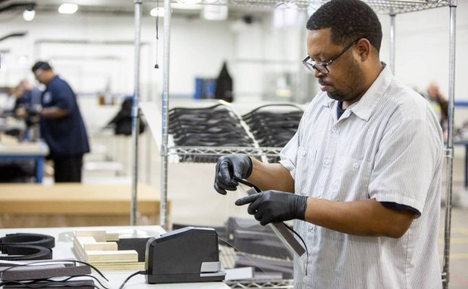 Мужчина на заводе по изготовлению защитных экранов