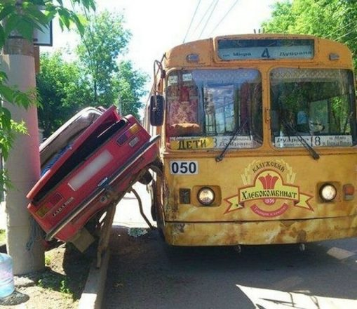 Машина застряла между столбом и троллейбусом