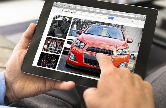 Человек смотрит в планшете машины
