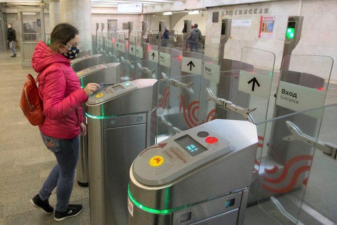 Девушка в маске проходит через турникет метро