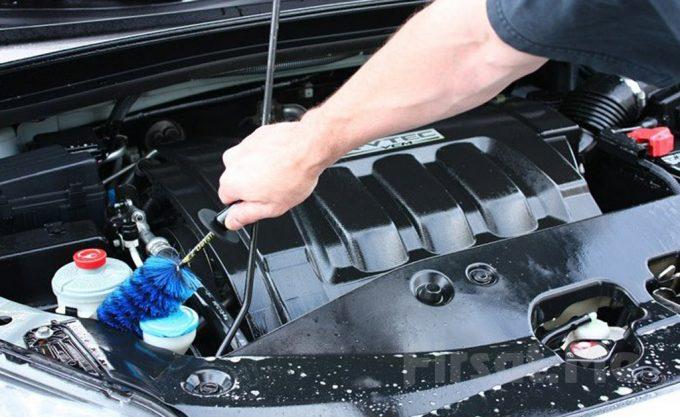 Мужчина чистит двигатель