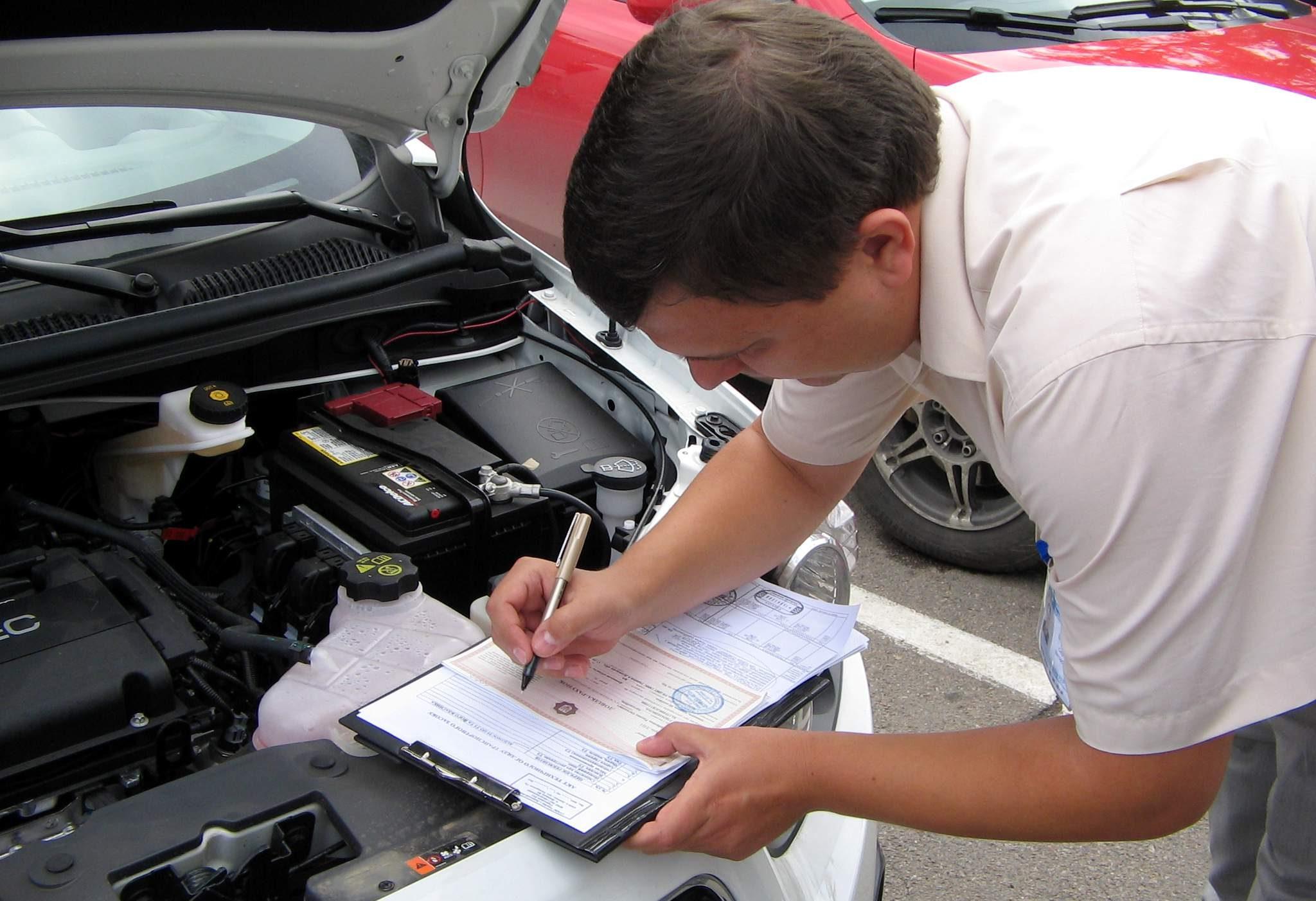 Мужчина возле машины подписывает документы