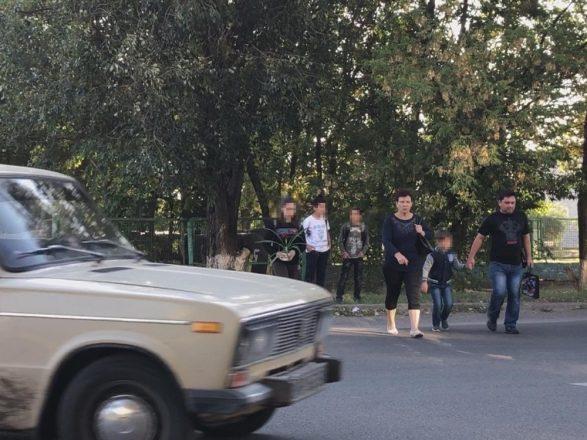 Люди переходят дорогу перед машиной