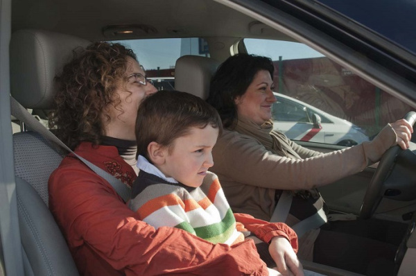 Ребенок в машине на руках у родителей