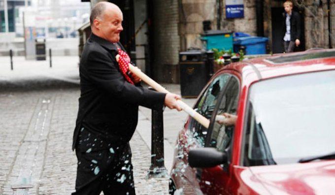 Мужчина битой разбивает стекло в машине