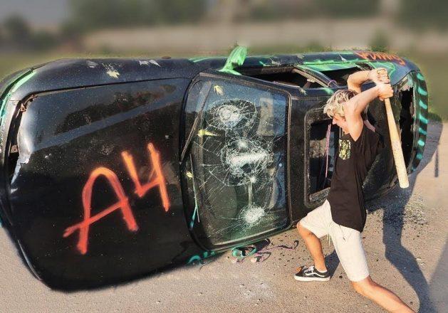 Парень разбивает машину битой