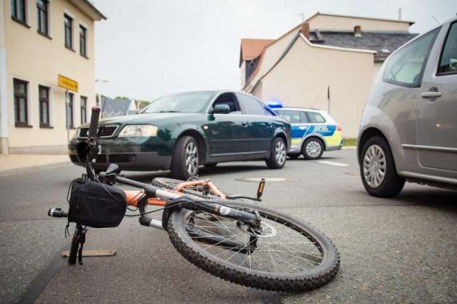 Велосипед на дороге и автомобиль