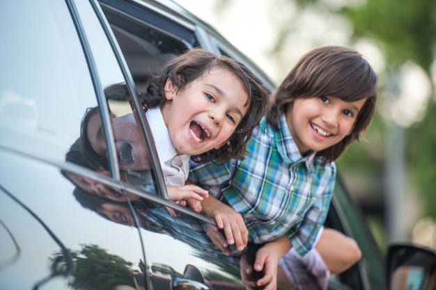 Дети выглядывают из окна машины