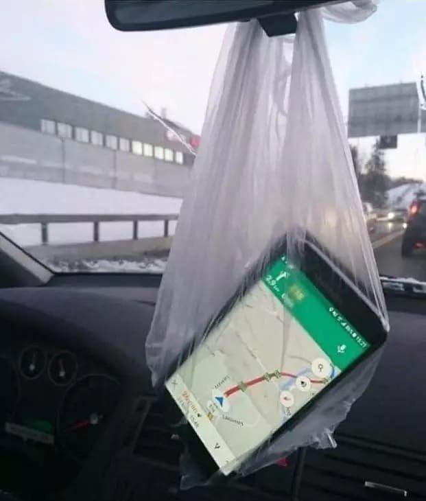 Смартфон в пакете на зеркале авто