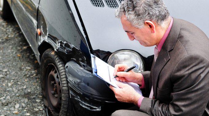 Мужчина заполняет документы возле машины