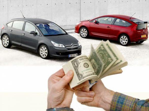 Пачка долларов на фоне двух авто