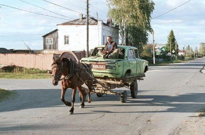 Телега с лошадью везет машину