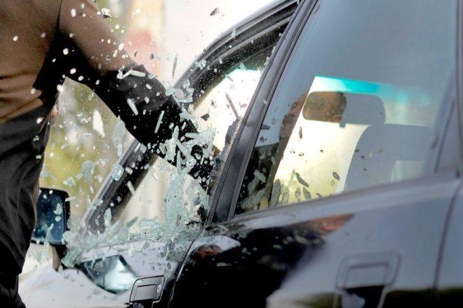 Мошенник разбивает водительское стекло.